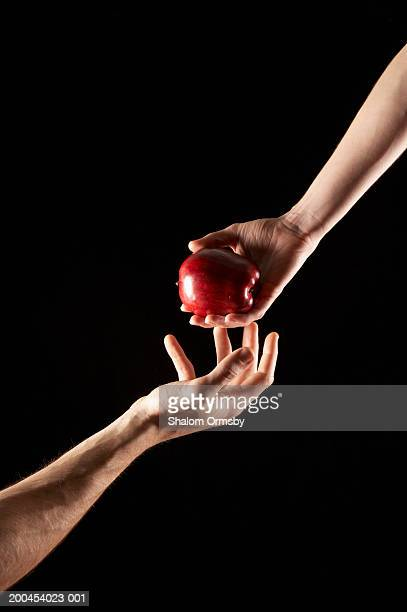 Hand passing apple to another hand