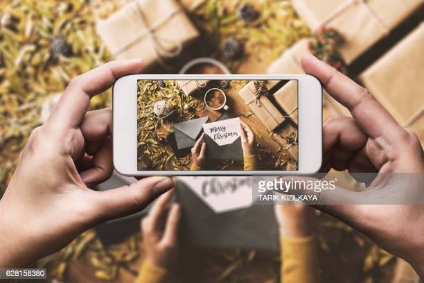 Hand photographing greeting cards, Christmas table top flat lay