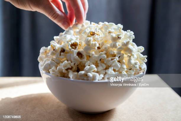 hand picking freshly made popcorn from the bowl - popcorn stock pictures, royalty-free photos & images