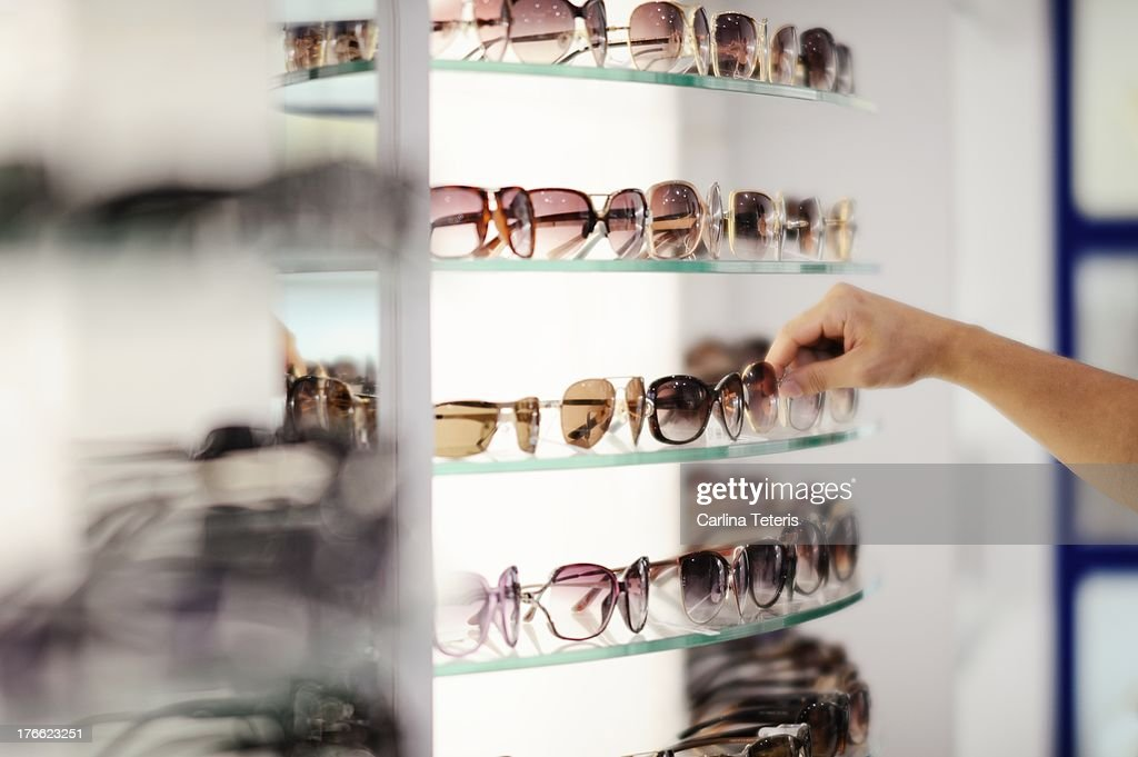 Hand picking out sunglasses from a store shelf : Stock Photo