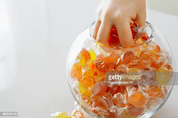 Hand picking sweets from jar, close up