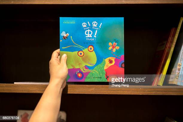 Hand picking up a picture book from a shelf in a book store According to a recent survey by China News Publishing Research Institute in 2016 85% of...