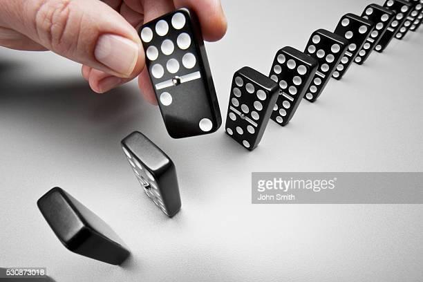 Hand picking up black domino