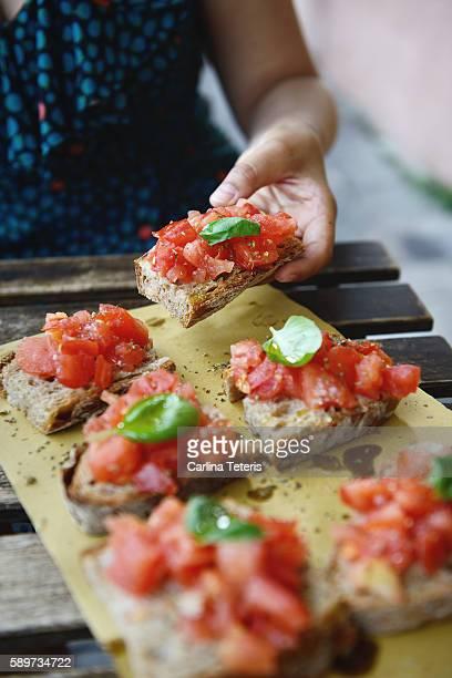 Hand picking up Italian bruschetta