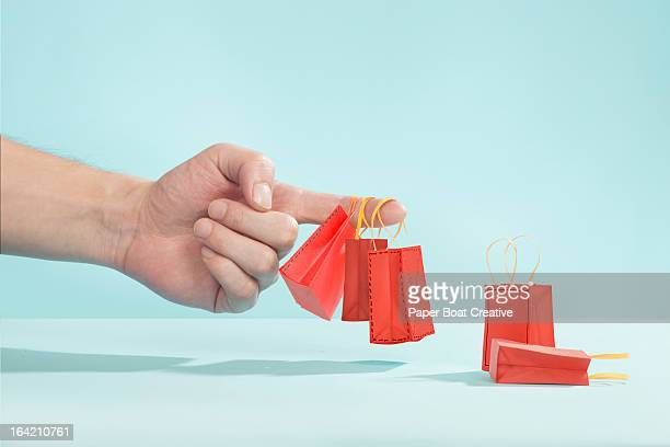 hand picking up tiny shopping bags on finger - group of objects stock pictures, royalty-free photos & images