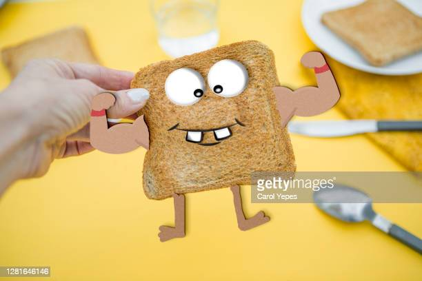 hand picking up toasted bread with google eyes - google stock pictures, royalty-free photos & images