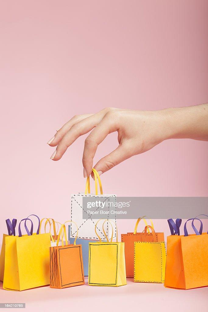 Hand picking up white tiny paper shopping bag : Stock Photo