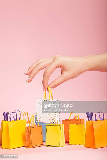 hand picking up white tiny paper shopping bag - shopping bag stock pictures, royalty-free photos & images