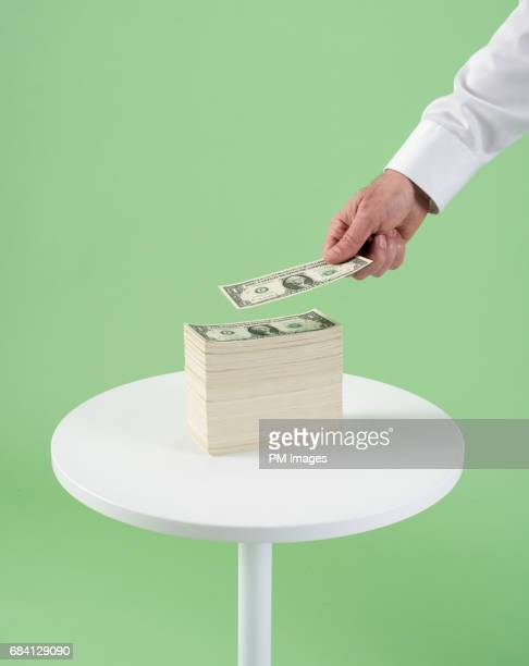 Hand placing 1 dollar on stack of dollars