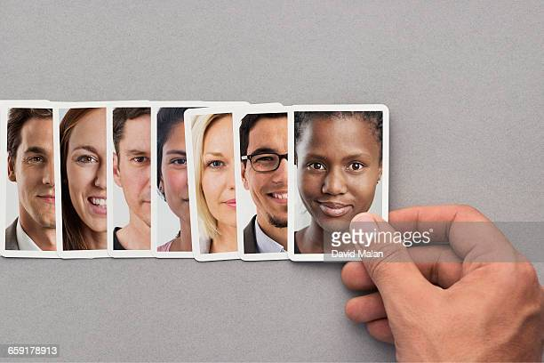 Hand placing a card with a portrait in a row.