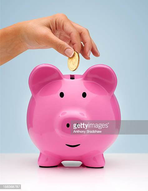 A hand placing a gold coin in a piggy bank