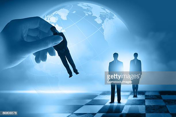 Hand placing businesspeople on checkerboard