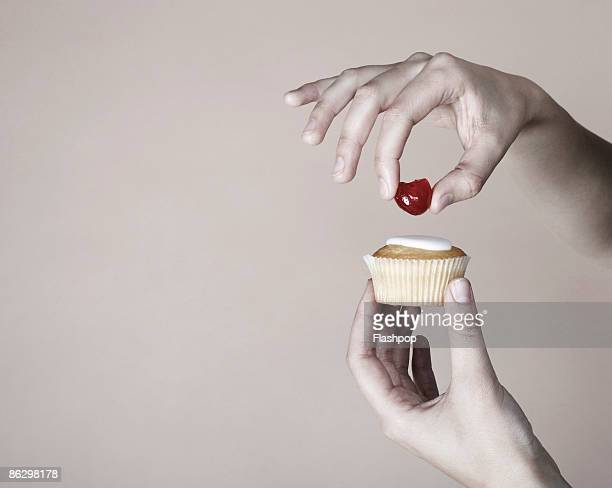 Hand placing cherry on top of cup cake