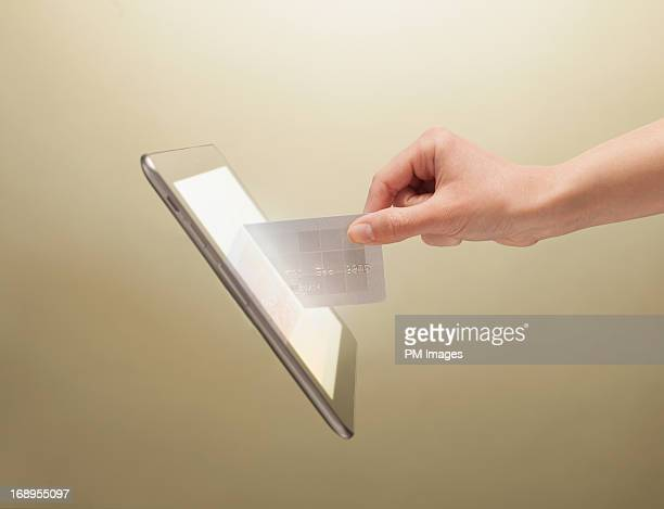 hand placing credit card into tablet - e commerce stock pictures, royalty-free photos & images