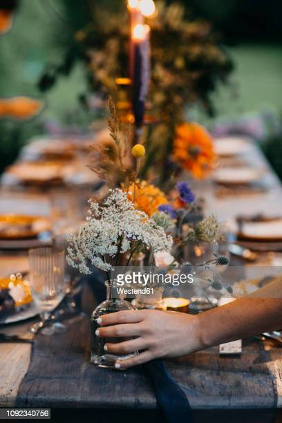 hand placing flower vase on festive laid table with candles outdoors - 位置付ける ストックフォトと画像