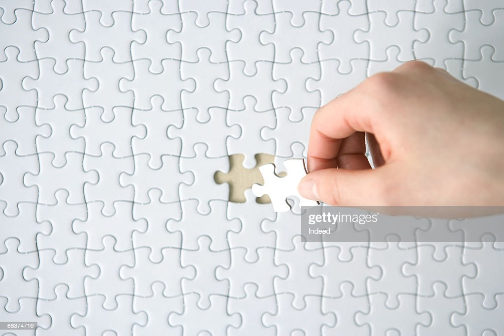 Hand placing last piece into blank jigsaw puzzle  : Stock Photo