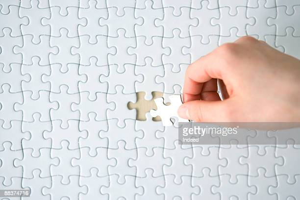 hand placing last piece into blank jigsaw puzzle  - raadsel stockfoto's en -beelden