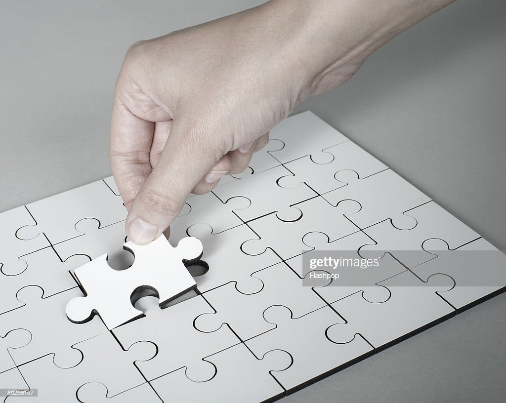 Hand placing last piece into jigsaw puzzle : Stock Photo