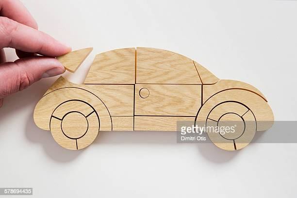 Hand placing last piece of wooden car puzzle