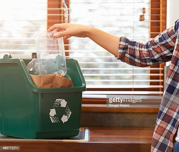 hand placing plastic into recycling bin. - carbon footprint stock pictures, royalty-free photos & images