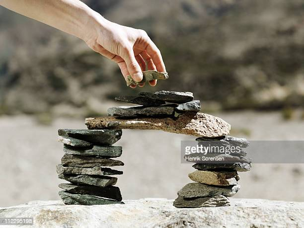 hand placing stone on balancing rock bridge - putting stock pictures, royalty-free photos & images