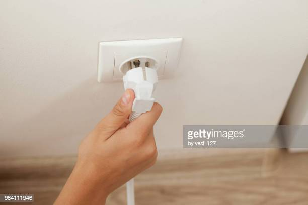 hand plugging in or out an electric cord into a socket - tomada - fotografias e filmes do acervo