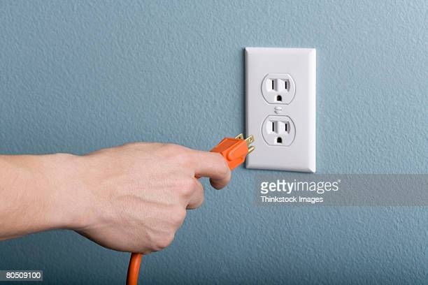 hand plugging power cord into outlet - plugging in stock pictures, royalty-free photos & images