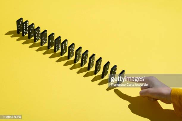 hand pointing at a row of dominoes - impact photos et images de collection