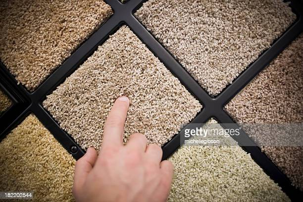 Hand pointing at a selection of carpet samples