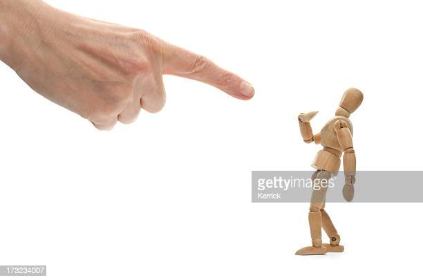 A hand pointing at a wooden mannequin