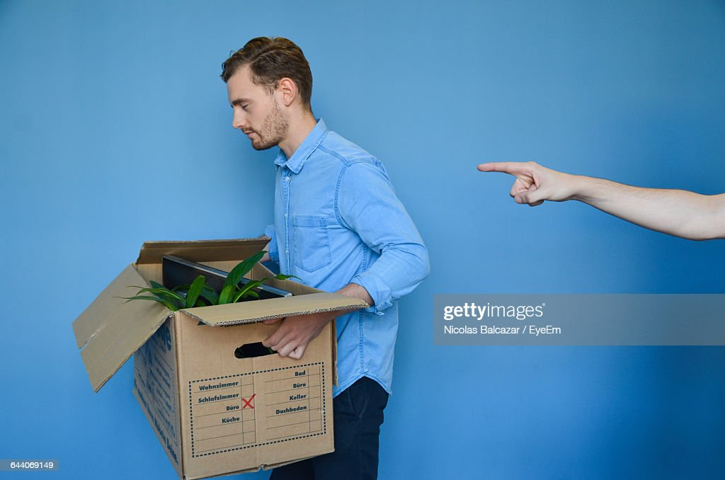 Hand Pointing At Young Man Carrying Cardboard Box After Getting Fired : Stock Photo