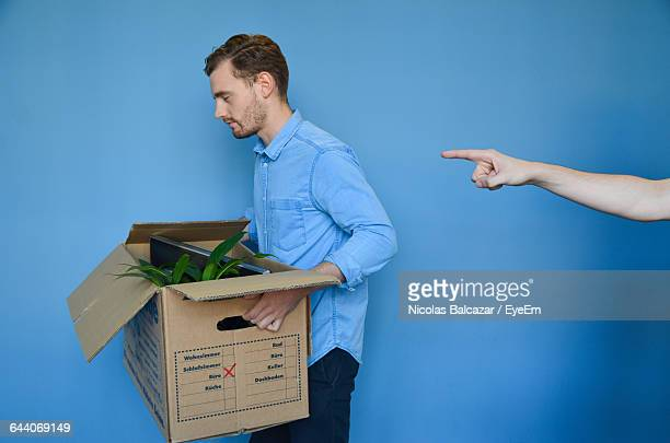hand pointing at young man carrying cardboard box after getting fired - downsizing unemployment stock pictures, royalty-free photos & images