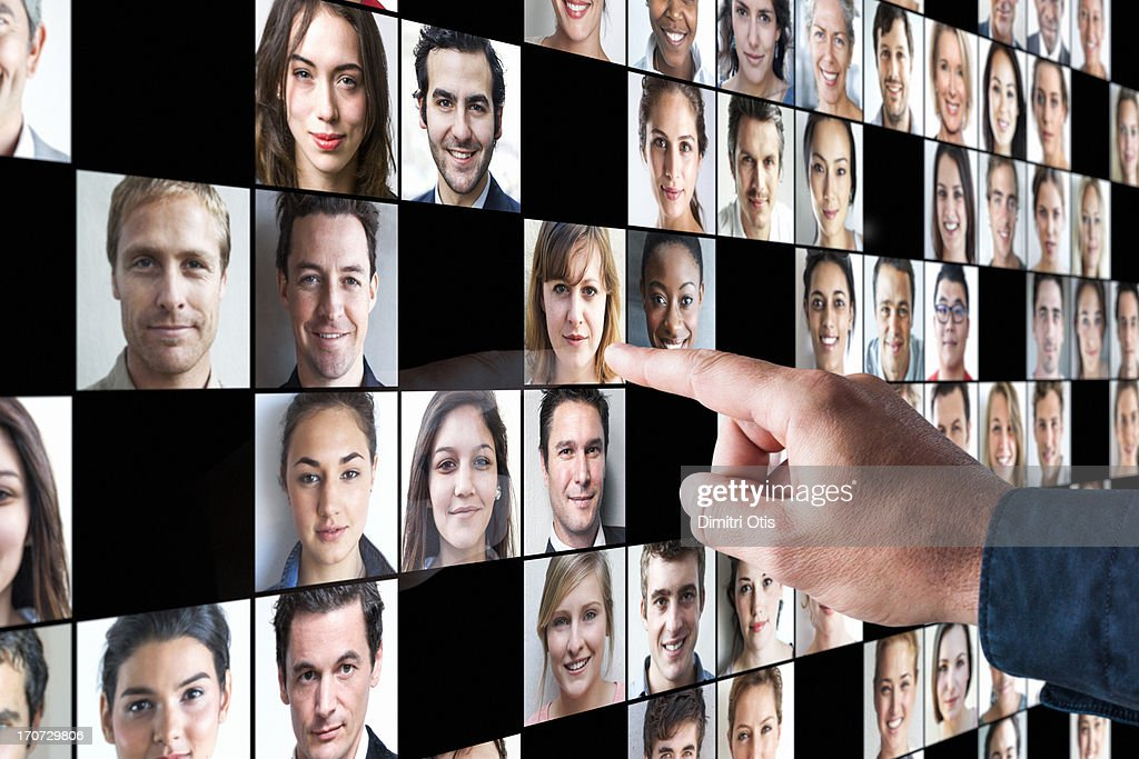 Hand pointing to portrait amongst many others : Stock Photo