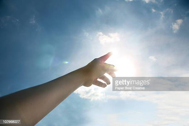 Hand pointing toward the sun and blue sky