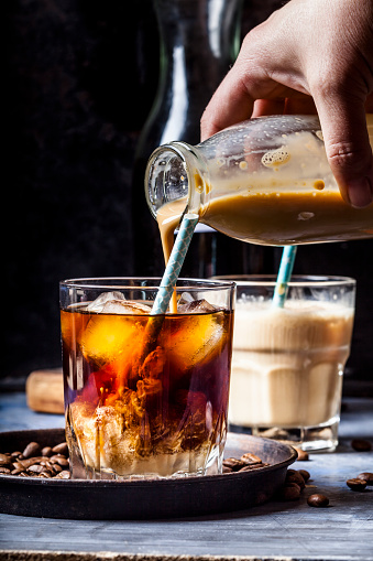 Hand pouring homemade vanilla flavoured coffee creamer into a glas with iced coffee - gettyimageskorea