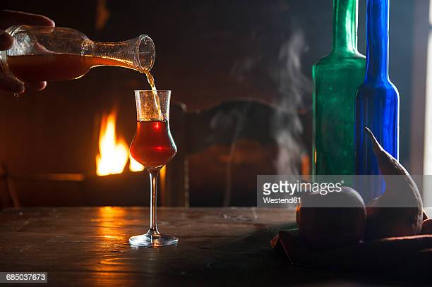 hand pouring liqueur into shot glass in front of open fire - liqueur stock pictures, royalty-free photos & images