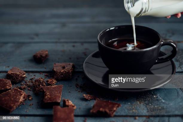 hand pouring milk into a cup of coffee with dark chocolate - coffee with chocolate stock pictures, royalty-free photos & images