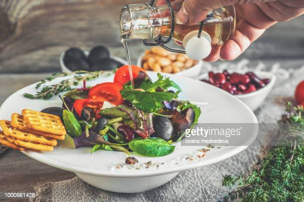Hand pouring olive oil salad diet for weight correction from the leaves of Lollo Rosso,...
