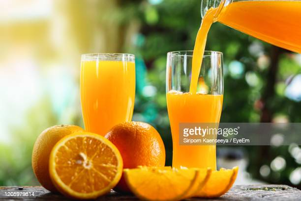 hand pouring orange juice on glasses - orange juice stock pictures, royalty-free photos & images