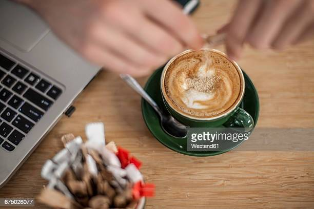 hand pouring sugar into cup of cappuccino next to laptop - sugar coffee stock photos and pictures