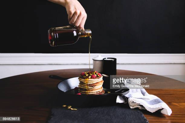 Hand pouring syrup on pancakes
