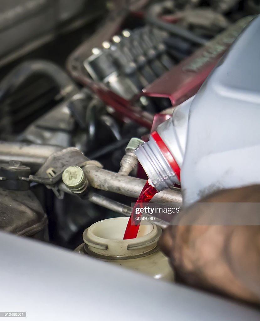 Hand pouring transmission fluid : Stock Photo