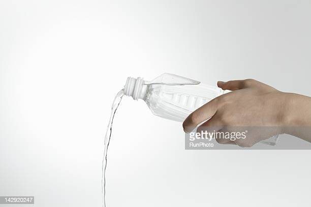 hand pouring water from bottle