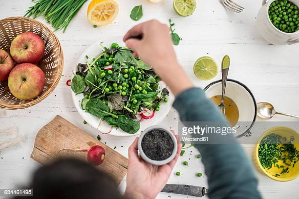 Hand preparing salad seasoning with black sesame