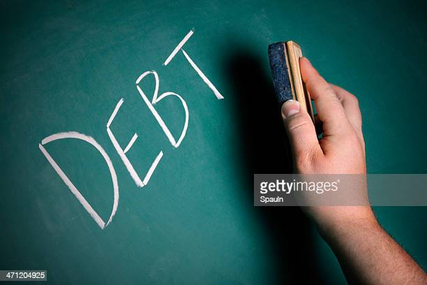 Hand preparing to erase the word DEBT from a chalkboard