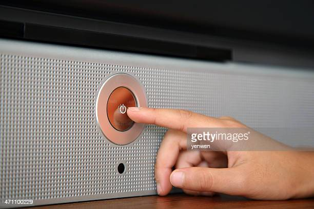 A hand pressing a silver power button on a speaker