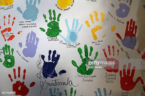 Hand prints of immigrants and volunteers adorn the wall of a migrants assistance center on December 2 2016 in Stamford Connecticut The nonprofit...