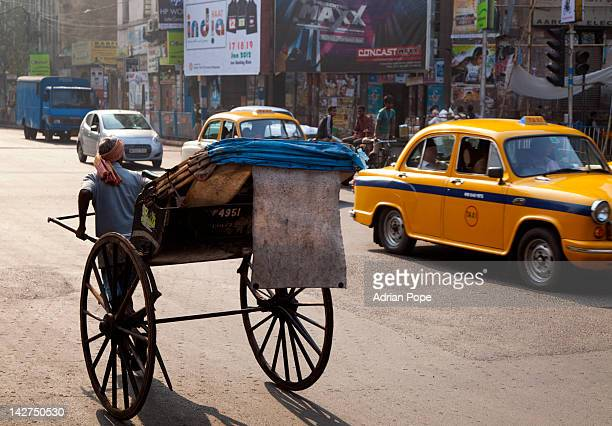 Hand pulled rickshaw and modern traffic, Calcutta