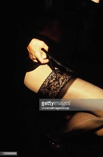 Hand Pulling Black Garter on Woman's Leg