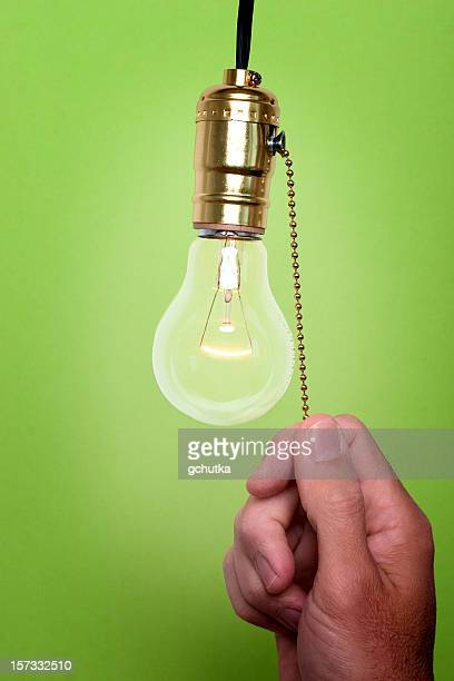 hand pulling chain to turn off light bulb green background - gchutka stock pictures, royalty-free photos & images